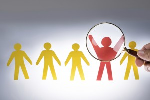 Cropped image of hand magnifying red paperman representing recruitment against gray background